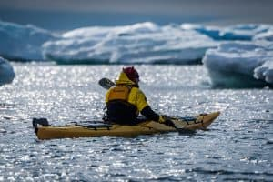 Backlit kayaker paddling past icebergs in sunshine
