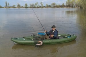 Man Catching Fish In Inflatable Kayak